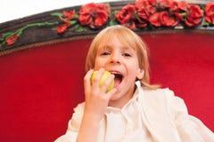白肤金发的孩子earing的苹果 免版税库存照片