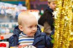 白肤金发的宝贝在超级市场推车坐并且选择一棵圣诞树在商店 免版税库存图片
