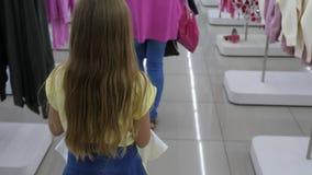 白肤金发的对试装间的女孩运载的衣裳精品店的 影视素材