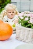 白肤金发的小女孩在桌上在庭院里 库存图片