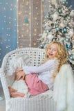 白肤金发的小女孩画象在圣诞节时间的一把椅子笑 图库摄影