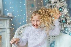 白肤金发的小女孩画象在屋子里坐并且接触她的在一把椅子的头发在圣诞节 免版税库存照片