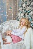 白肤金发的小女孩画象并且微笑坐在圣诞节时间的一把椅子 库存照片