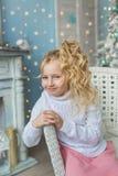 白肤金发的小女孩画象并且微笑坐在圣诞节的一把椅子在屋子里 图库摄影