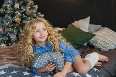 白肤金发的小女孩画象蓝色礼服的在圣诞节暗室说谎并且看起来旁边在一张床上 库存照片