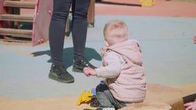 白肤金发的小孩使用与在操场的玩具拖拉机 股票录像