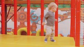白肤金发的小孩站立黄色表面上他们他的母亲approahes他 股票录像