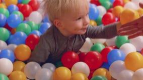白肤金发的小孩设法离开大量小的球和由他的母亲` s手帮助 股票视频
