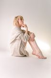 白肤金发的少妇在大白色开士米毛线衣和就座穿戴了在白色整个层上 库存照片