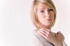 白肤金发的少妇在大白色开士米毛线衣穿戴了 免版税库存图片