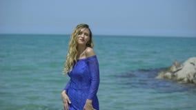 白肤金发的少妇在天蓝色的海岸、海滩或者码头唱歌 性感的女孩歌手唱歌,舞蹈,执行,诱惑,挥动 股票录像