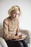白肤金发的少妇文字在她的学报上 免版税库存照片