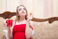 白肤金发的少妇饮用的茶和吃蛋糕  免版税图库摄影
