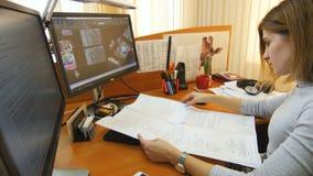 白肤金发的工作者坐在计算机并且探索图画 股票录像