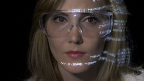 白肤金发的工程师妇女佩带的玻璃和研究编程的代码,当信息在她的面孔被反射-时 股票录像