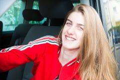 白肤金发的微笑的司机女孩在van car在夏天 库存图片