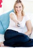 白肤金发的微笑的电视注意的妇女 图库摄影