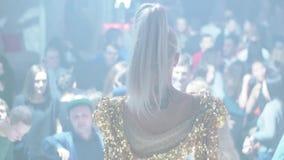 白肤金发的戈戈舞的舞蹈家的后部发光的衣服的在拥挤夜总会阶段  股票录像