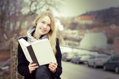 白肤金发的户外书俏丽的读取妇女 库存照片