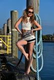 白肤金发的摆在码头的妇女佩带的水手短裤和性感的上面 免版税库存照片
