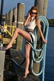 白肤金发的摆在码头的妇女佩带的水手短裤和性感的上面 免版税图库摄影