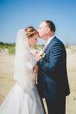 白肤金发的新娘和新郎在沙子 免版税库存照片