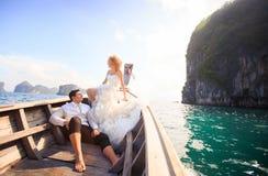 白肤金发的新娘和英俊的新郎小船的 库存图片