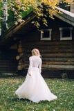 白肤金发的新娘在木房子背景的振翼的礼服走 回到视图 附庸风雅 免版税库存照片
