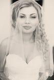 白肤金发的新娘看起来华美摆在窗口后 免版税库存图片