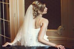 白肤金发的新娘看起来华美摆在窗口后 免版税库存照片
