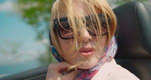 白肤金发的时髦有风妇女微笑的愉快的驾驶的敞蓬车时尚自然构成4k旅行一画象移动的头发 股票录像
