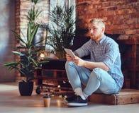 白肤金发的时髦的男性的充分的身体图象使用片剂个人计算机的 免版税库存图片