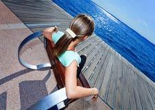 白肤金发的椅子女孩松弛海边 免版税库存照片