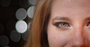 白肤金发的模型以非凡黑暗和在被弄脏的光bokeh背景的发光的构成半面孔射击  影视素材