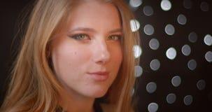 白肤金发的模型外形射击与闪烁诱惑在bokeh背景的构成微笑的照相机 股票录像