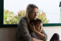 白肤金发的母亲微笑并且抱她的在她的胳膊之间的幼儿 免版税库存图片