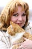 白肤金发的猫拥抱的妇女 免版税库存图片