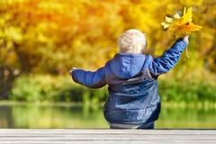 白肤金发的男孩坐河码头 黄色叶子在手上 bac 库存照片