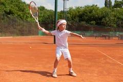 白肤金发的男孩实践的网球 免版税库存照片