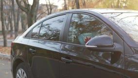 白肤金发的男孩对黑汽车打开门并且坐在汽车座位的位子 股票视频
