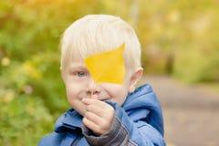 白肤金发的男孩拿着在他前面的一片黄色叶子 画象 免版税库存照片