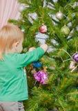 白肤金发的男孩装饰圣诞树 免版税库存照片