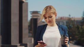 白肤金发的白种人出现清早在街道,饮用的咖啡和短信上与她的朋友的 影视素材