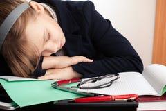 白肤金发的白种人女小学生在书桌上睡觉 库存图片