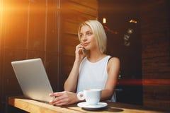 白肤金发的白种人妇女谈话在手机在便携式的便携式计算机上的工作期间 图库摄影