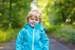 白肤金发的矮小的小孩男孩画象蓝色防水raincoa的 免版税库存图片