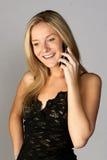 白肤金发的移动电话微笑的联系的妇&# 免版税库存图片