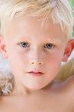 白肤金发的穿蓝衣的男孩结算眼睛闪&# 图库摄影