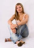 白肤金发的纵向坐的妇女年轻人 免版税库存图片