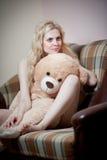 年轻白肤金发的肉欲的妇女坐放松与一个巨大的玩具熊的沙发 库存图片